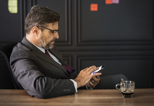 muž klikající do mobilu